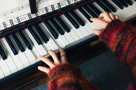 piano: The hands of a young woman as she is playing the piano