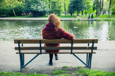 A young woman is sitting and relaxing on a bench in the park by a pond Stockfoto