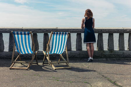 balustrades: A young woman is standing by a wall with concrete balustrades on a promenade and is admiring the sea, there are two deck chairs next to her