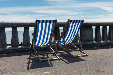 balustrades: Two deck chairs on a promenade by the seaside with concrete balustrades