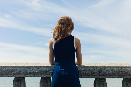 balustrades: A young woman wearing a blue dress is standing by a wall with concrete balustrades on a promenade and is admiring the seaside on a sunny day