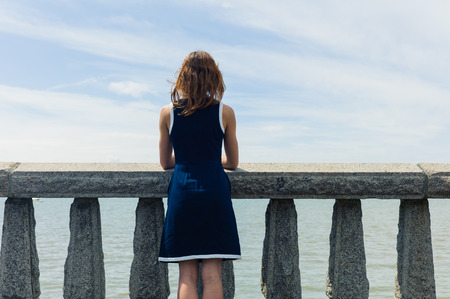 A young woman wearing a blue dress is standing by a wall with concrete balustrades on a promenade and is admiring the seaside on a sunny day