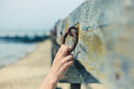 grabbing: A young female hand is grabbing an old rusty chain attached to a wooden beam