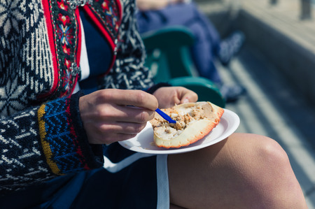 A young woman is eating a dressed crab outside on a sunny day