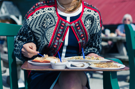 garden eel: A young woman is eating cokcles and smoked fish outside on a sunny day Stock Photo