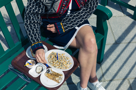 A young woman is eating cokcles and smoked fish outside on a sunny day Stock Photo