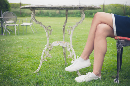 lawn chair: A young woman is sitting and relaxing on a chair on a  lawn in a garden Stock Photo