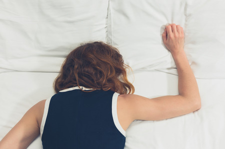 passed out: A young woman wearing a dress is passed out on a bed