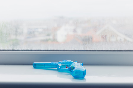 window sill: A blue toy gun on a window sill