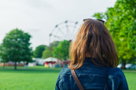 A woman in a park is looking at a fun fair