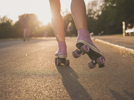 skate park: The legs of a young woman as she is roller skating in a park at sunset