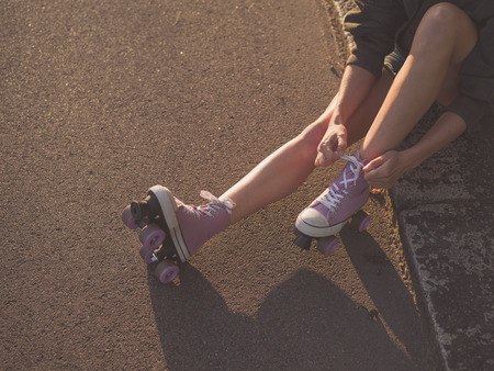roller: A young woman is sitting on the ground and is putting on roller skates in the park at sunset Stock Photo