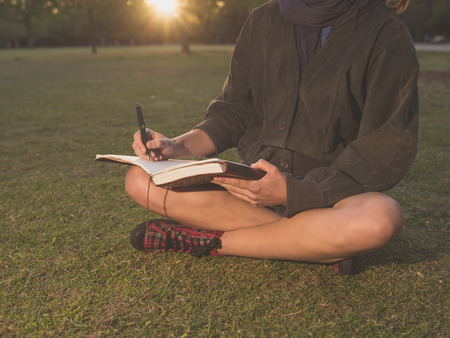 memoir: A young woman is sitting on the grass in a park at sunset and is writing in a notebook