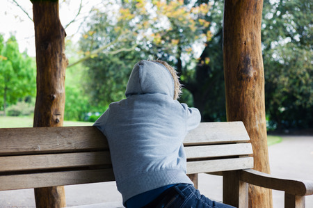 hooded top: A young person wearing a hooded top is sitting in a shelter in the park Stock Photo
