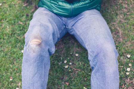 scraped: A trendy young man with a hole torn in his jeans at the knee is sitting on the grass