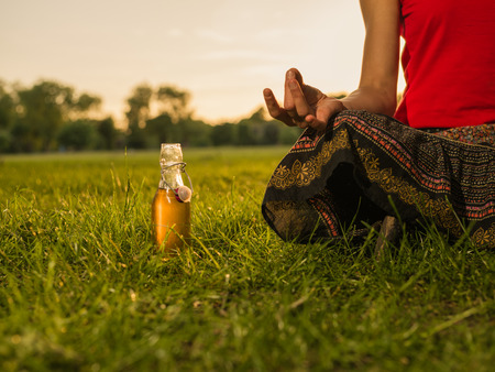A young woman is meditating in a park at sunset, there is a bottle of health drink next to her