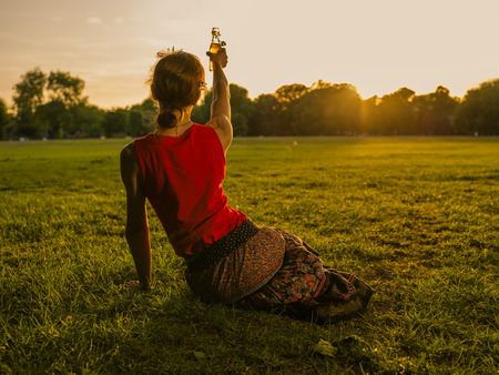 A young woman is drinking in a park and is lifting her bottle saluting the sunset Stock Photo