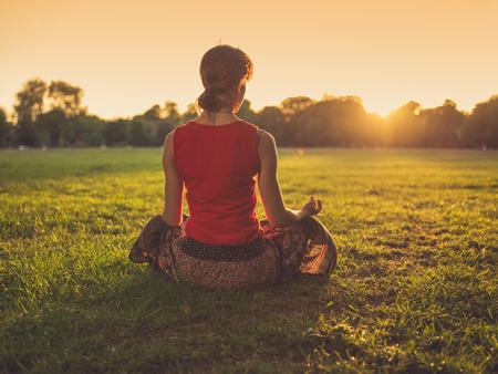 젊은 여자가 공원에서 잔디에 앉아 일몰에 명상이다