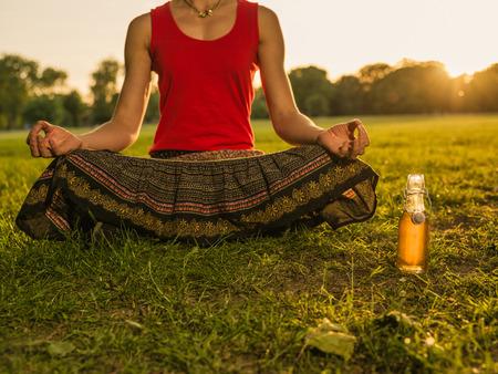 若い女性は夕暮れ時の公園で瞑想、彼女の隣に健康ドリンクのボトルがあります。 写真素材