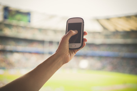 sporting event: A female hand is holding a smart phone in a stadium to take pictures of a sporting event Stock Photo