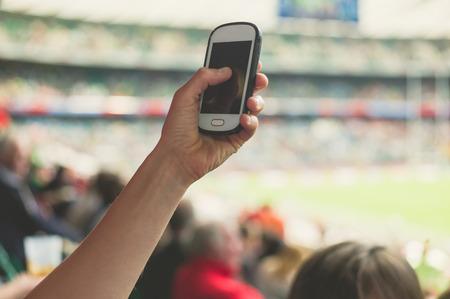 menschenmenge: Eine weibliche Hand h�lt ein Smartphone in einem Stadion, Bilder von einer Sportveranstaltung nehmen