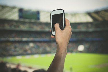 A female hand is holding a smart phone in a stadium to take pictures of a sporting event Stock Photo