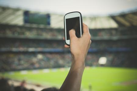 deporte: Una mano femenina está sosteniendo un teléfono inteligente en un estadio para tomar imágenes de un evento deportivo Foto de archivo