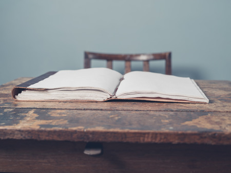 old desk: An open notebook on an old wooden desk