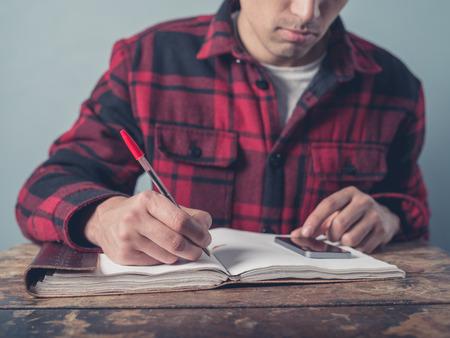 hombre escribiendo: Un hombre joven que llevaba una chaqueta a cuadros está utilizando un teléfono inteligente y está tomando notas en un bloc de notas en un escritorio Foto de archivo