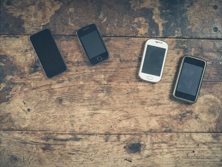 cell phone screen: A selection of smart phones on a wooden table