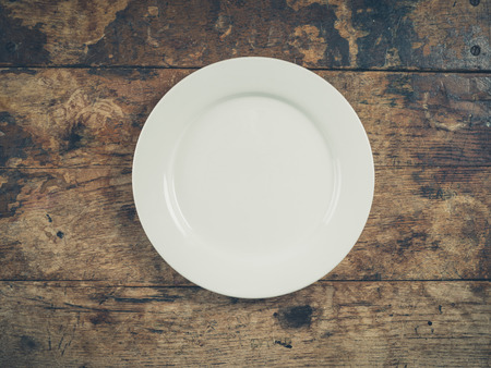 overhead: Overhead shot of a white plate on a wooden table