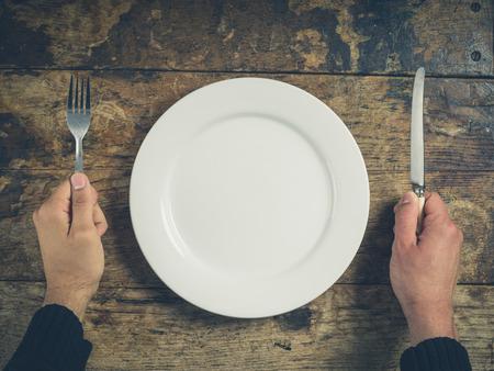 木製テーブルの上の白い皿をナイフとフォークを持って手のオーバー ヘッド ショット