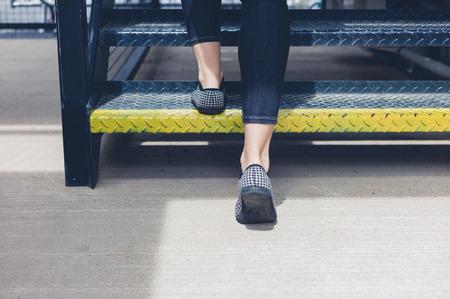 젊은 여자의 발은 그녀는 일부 금속 계단을 걷고로 스톡 콘텐츠