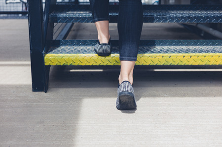The feet of a young woman as she is walking up some metal stairs