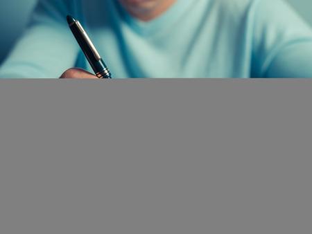 estudiantes de secundaria: Un joven está sentado en una mesa y está escribiendo en un cuaderno Foto de archivo