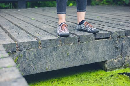 pieds sales: Les pieds d'une jeune femme debout sur une terrasse en bois par un �tang sale avec des algues