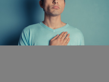 A young man wearing a blue jumper is placing his hand on his chest