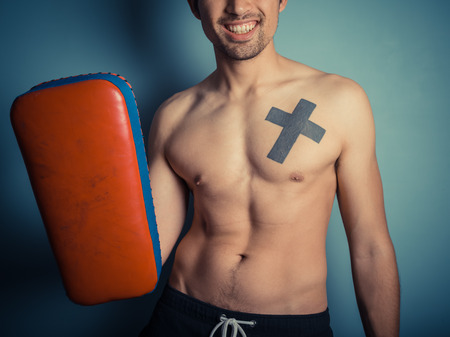 mixed martial arts: An athletic young shirtless man is holding pads and is ready for some muay thai or mixed martial arts training