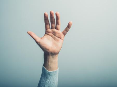 symbol hand: Eine m�nnliche Hand, befindet sich vor einer blauen Wand winken Lizenzfreie Bilder