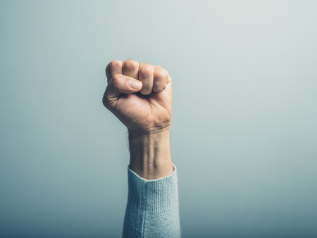 A clenched male fist is up in the air Stock Photo
