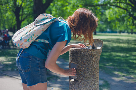 water park: A young woman is drinking from a water fountain in a park on a sunny day in the summer