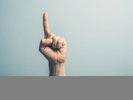 dedo indice: Una mano masculina con el dedo índice apuntando hacia arriba
