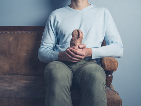 A young man is sitting on an old sofa and is holding a strange looking sweet potato