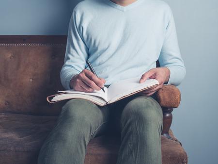 若い男は、古いソファに座っているとノートに書いています。