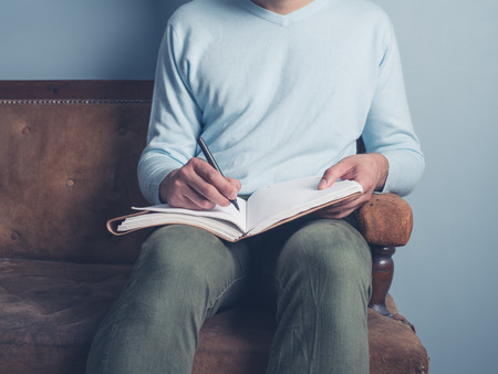 male  man: A young man is sitting on an old sofa and is writing in a notebook