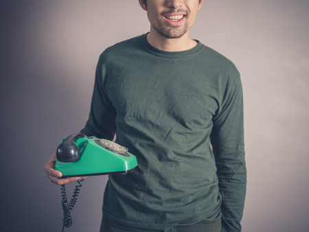 rotary phone: A happy young man is holding a vintage rotary phone
