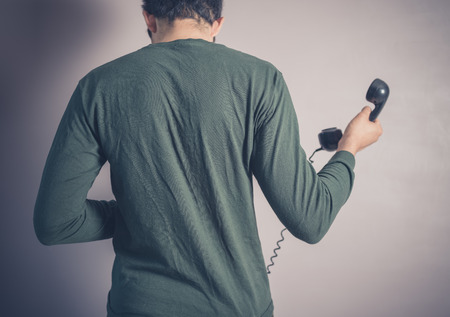 old fashioned rotary phone: Rear view shot of a young man using a vintage rotary telephone Stock Photo