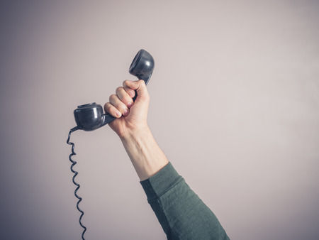 The hand of a young man is holding a vintage rotary telephone