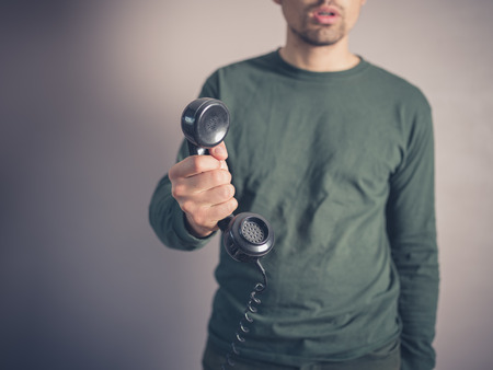 rotary phone: A concerned and worried looking young man is holding the receiver of a vintage rotary phone Stock Photo