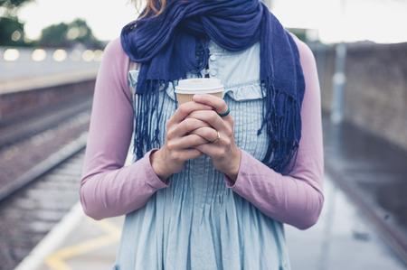 若い女性がコーヒーのカップを持つプラットフォームに立っていると電車を待っています。